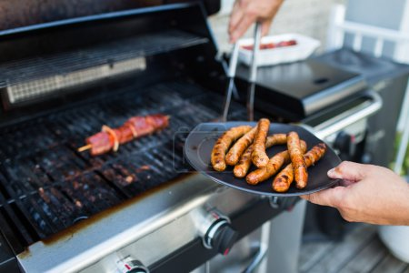 BBQ with sausages and red meat on the grill - male...