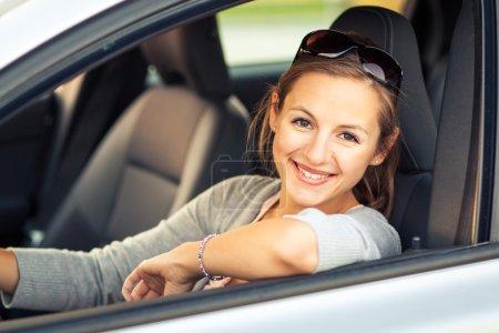 Photo pour Jolie jeune femme conduisant sa nouvelle voiture (image tonique de couleur, peu profonde DOF ) - image libre de droit