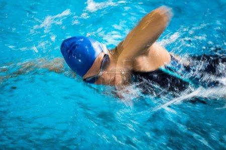 Photo pour Femme nageuse dans une piscine intérieure - rampant (peu profond DOF ) - image libre de droit