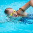Young girl in goggles and cap swimming crawl strok...