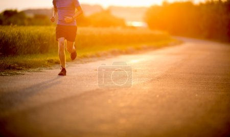 Male athlete or runner running on road