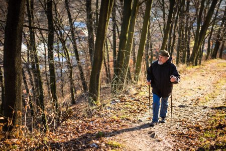 Photo pour Senior homme nordique marche, profiter de l'extérieur, l'air frais, obtenir l'exercice nécessaire - image libre de droit