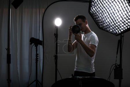 Photo pour Jeune photographe pro avec appareil photo numérique - DSLR et un énorme téléobjectif dans son studio bien équipé, prenant des photos (image couleur tonique ; peu profonde DOF ) - image libre de droit