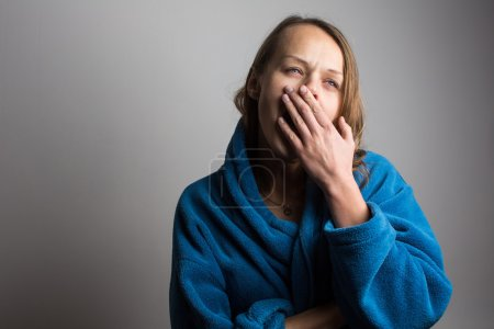 Sleepy young woman with wide open mouth yawning