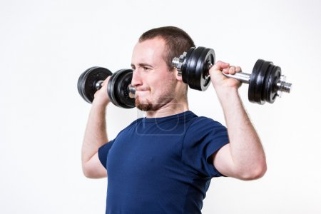Close up of young man lifting weights over white background