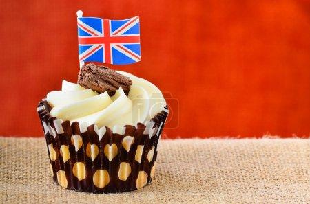Photo pour Gâteau au chocolat avec glaçage fondant et un flocon, couronné par le drapeau de l'Union jack, un concept de grand succès Britannique - image libre de droit