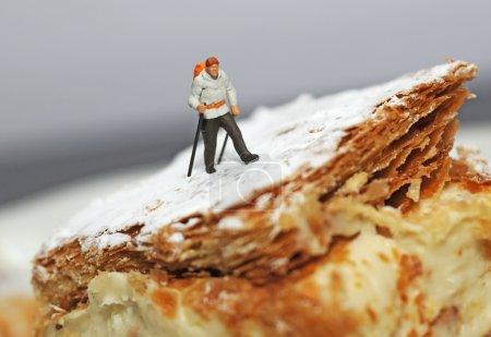 Photo pour Petite figurine de randonneur marchant sur un morceau de gâteau avec du sucre de ricin imitant la neige - image libre de droit