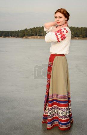 Photo pour Young woman in a Slavic Belarusian national original suit outdoors - image libre de droit