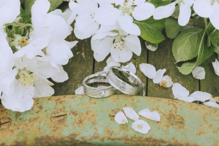 Photo for Still life of two wedding rings nicely arranged on a wooden background with white apple blossoms - Royalty Free Image