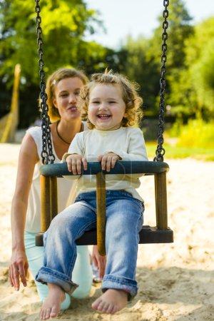 Foto de La madre y del niño hacia fuera junto a los columpios en el patio de recreo. - Imagen libre de derechos