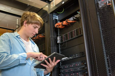 Photo for IT specialist configuring servers in climate controlled datacenter - Royalty Free Image