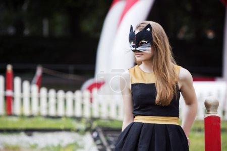 Photo pour Jeune femme avec un masque sur fond de parc d'attractions - image libre de droit