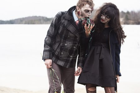 Young female feeding her zombie boyfriend