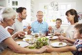 Rodina se modlí před jídlem doma