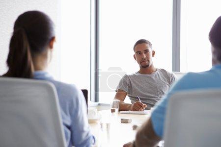 Businesspeople Having Meeting In Boardroom
