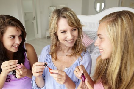 Mother and daughters painting nails