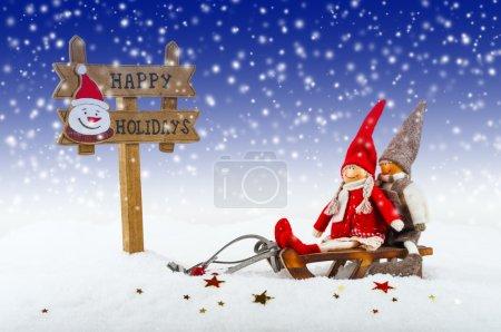 Photo pour Décorations de Noël : poupées sur luges et enseignes Joyeuses fêtes - image libre de droit