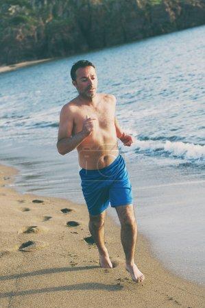 Handsome man running on the sunset sandy beach