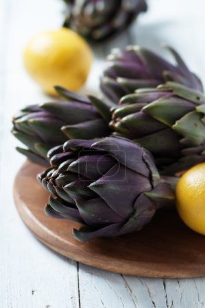 Raw fresh artichocke on the wooden table