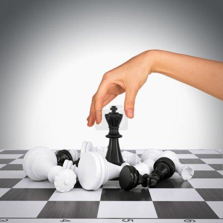 Woman hand touching king figure on chess board