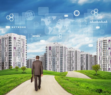 Businessman walking along road through green hills. City of tall buildings as backdrop. Charts and other virtual items in sky