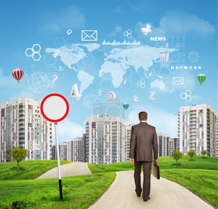 Businessman walking along road through green hills towards city. Charts and other virtual items in sky
