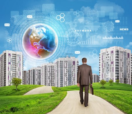 Businessman walking along road through green hills towards city. Brightly coloured planet, charts and other virtual items in sky.
