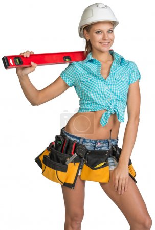 Beautiful girl in white helmet, shorts and shirt holding builders level on the shoulder