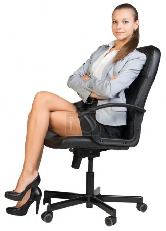 Photo for Businesswoman on office chair, looking at camera, with her back straight and her arms crossed on her breast. Isolated over white background - Royalty Free Image