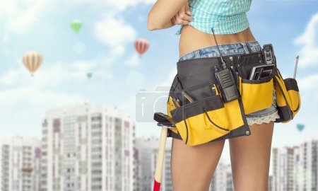 Photo for Woman in tool belt with different tools standing backwards, arms crossed. Cropped image. High-rise residential buildings and hot air balloons in background - Royalty Free Image