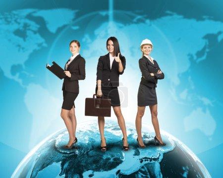 Photo pour Femmes d'affaires en costumes, chemisiers, jupes, souriant et regardant la caméra. Dans le contexte de la carte du monde et du globe. Éléments de cette image fournis par la NASA - image libre de droit