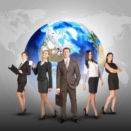 Photo pour Femmes et hommes d'affaires en costume, souriant et regardant la caméra. Dans le contexte du globe et de la carte du monde. Éléments de cette image fournis par la NASA - image libre de droit