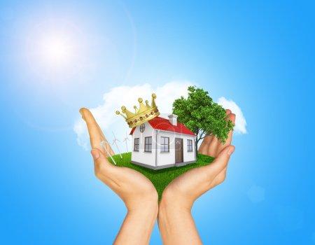 Foto de Manos sosteniendo la casa sobre hierba verde con corona, techo rojo, chimenea, árbol, turbina de viento. Nubes de fondo y cielo azul - Imagen libre de derechos