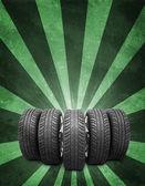 Klín nových kol automobilů. Zelené pozadí je beton a pruhy na dně