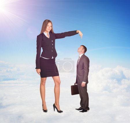 Photo for Small businessman looking up at large woman in suit. Clouds and cement surface as background. Business concept - Royalty Free Image