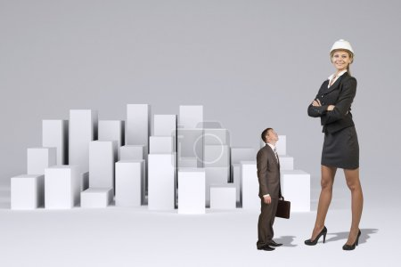 Small businessman looking at large businesswoman.