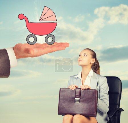Photo pour Jeune femme assise sur une chaise et regardant les hommes tenir la main chariot bébé - image libre de droit