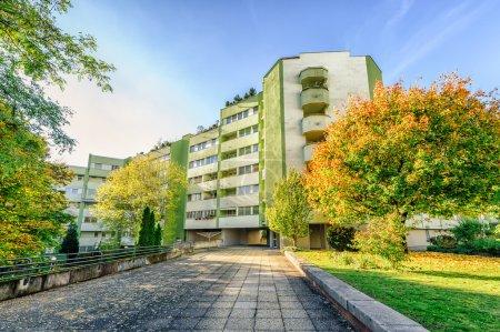 Photo pour Modern apartment building with autumn colored trees - image libre de droit