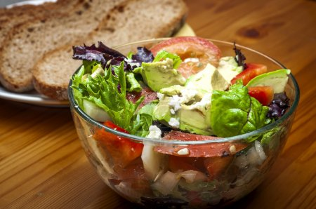Bowl of salad with feta cheese, tomatos, avocado, leafy greens, red peppers, and onions on a wooden table with rustic sliced bread in the background