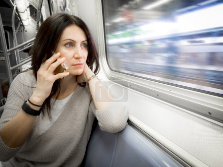 Photo for Woman in her 30s is riding the subway ans looking out the windows, holding a hand under her neck while the subway is moving - Royalty Free Image