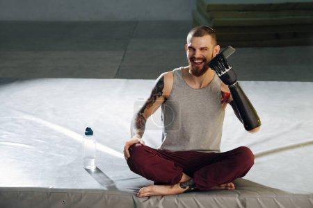 Photo pour Homme cyborg drôle essayant de tenir son téléphone avec la main bionique, riant. Il est assis sur un tapis jambes croisées, prenant une pause des exercices phisiques. Beaux tatouages sur les épaules. Vue frontale. - image libre de droit