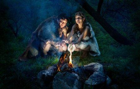 Cave people dressed in animal roast oneself at bon...