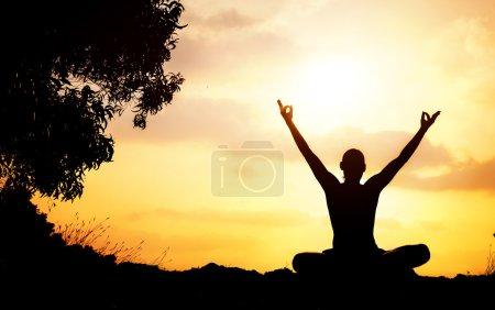 Photo pour Silhouette de l'homme dans la méditation d'yoga posent avec montantes mains près de l'arbre au coucher du soleil à gokarna, karnataka, Inde - image libre de droit