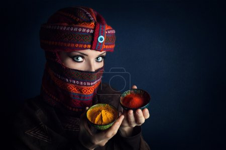 Photo for Oriental woman in turban offering red chili and yellow turmeric powders at bazar - Royalty Free Image