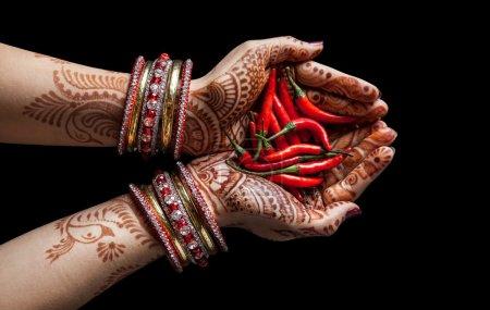 Photo pour Mains de femme avec henné tenant le chili rouge isolé sur fond noir avec chemin de coupe - image libre de droit