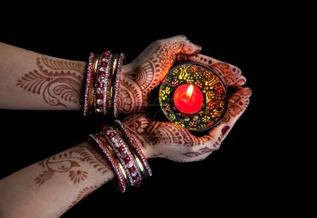 Woman hands with henna holding candle isolated on ...