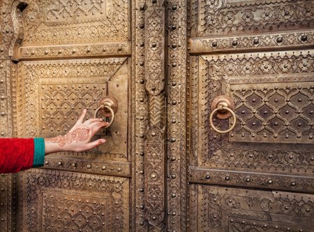 Photo pour Woman hand with henna painting opening golden door in City Palace of Jaipur, Rajasthan, India - image libre de droit
