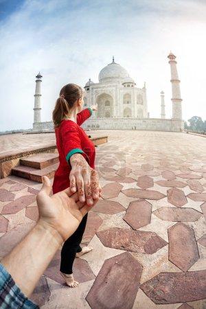 Photo pour Femme en costume indien rouge tenant l'homme à la main et pointant vers Taj Mahal à Agra, Uttar Pradesh, Inde - image libre de droit