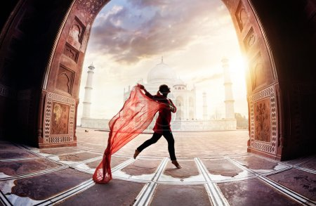 Photo for Woman with red scarf dancing near Taj Mahal in Agra, Uttar Pradesh, India - Royalty Free Image