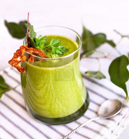 Photo pour Smoothie vert décoré avec du persil et sec fruit proche jusqu'à restaurant - image libre de droit